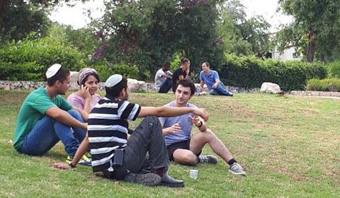 יושבים בדשא של הכפר